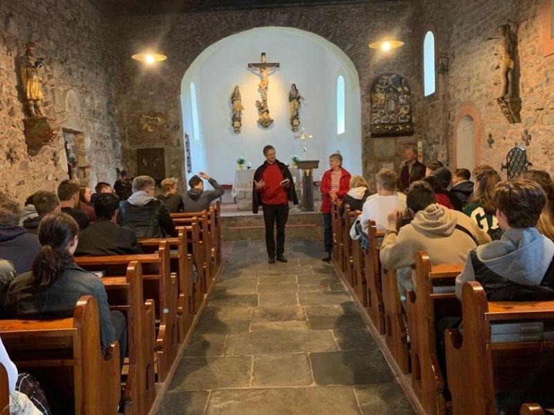 Bild 12:  Pater Hanzej Rosenzopf mit den Schülerinnen und Schülern in Karnburg